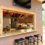 Rustic wooden framed bar with red window and marmer for serving table and black leather stools under big TV screen