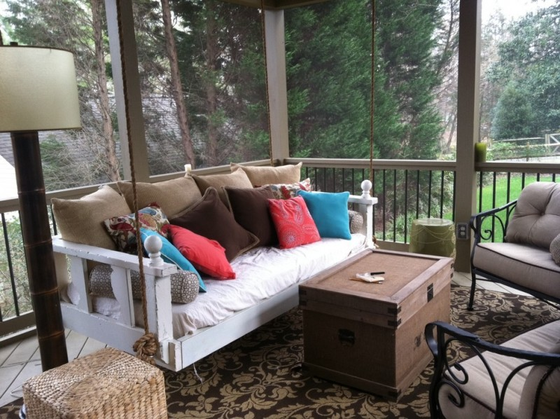 White wooden bed swing for porch with brown, red, and bue pillows and white bed cushion