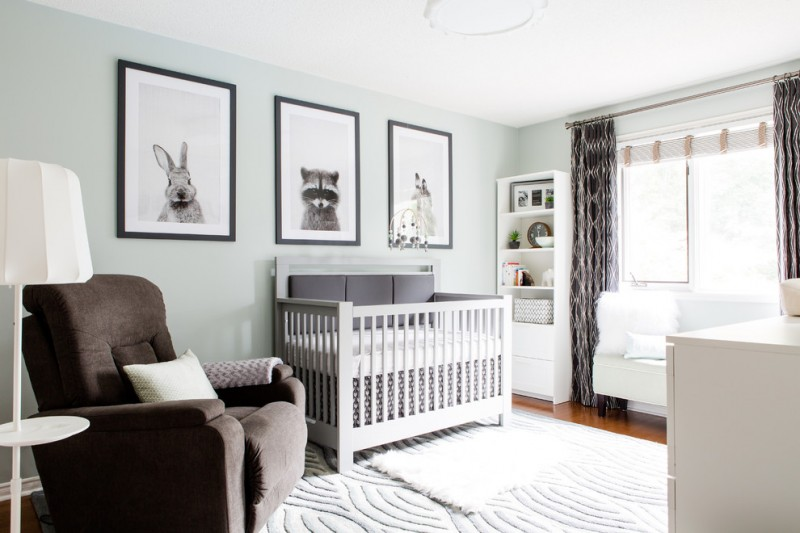 baby boy room with white rug, dark brown couch, three paintings of rabbit, donkey and raccoon, charcoal grey curtain, white grey crib, and white fluffy pillows