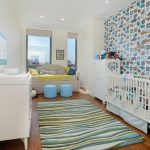 Blue Animal Theme With Blue Wallpaper On One Side, White Cribs, Blue White Brown Rug, Light Blue Small Ottoman, White Sofa, White Cabinet, White Diaper Changing Cabinet, And Toys