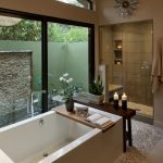 built in bathtub pebble floor glass window comfy shower space white pendant light