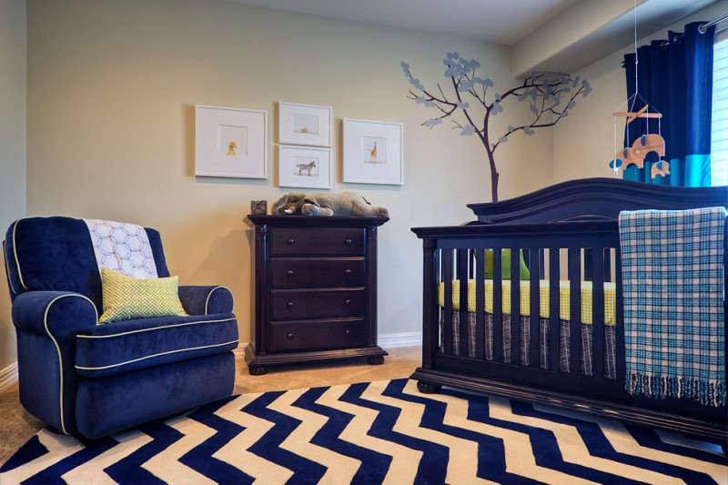 dark blue theme room with blue white zigzag rug, blue couch with yellow edges, blue crib,blue curtain, wooden cabinet and blue tree sticker onthe wall