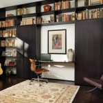 dark wooden built in bookshelves floor to ceiling bookshelves white backwall two storage cabinet