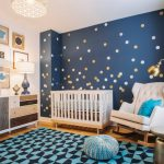galaxy baby boy theme with blue night sky wallpaper at one side, white cribs, white couch, white brown cabinet, golden lamps and paintings