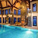 indoor pool poolside seating chandeliers wooden ceiling windows wall lamps fireolace low table