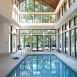 indoor pool wooden ceiling poolside chairs white walls glass windows glass doors mini indoor pool