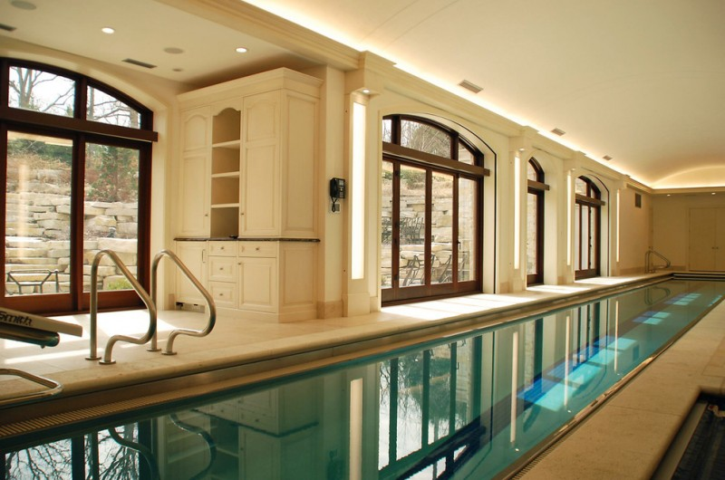 long indoor pool ceiling lights big glass windows white ceiling cabinet shelf door modern lamps