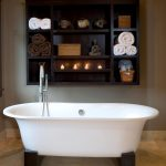 modern free standing bathtub dark wooden floating shelves light porcelain floor