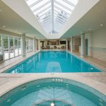 modern indoor pool poolside chairs pillars ceiling lights glass light colors transparent roof