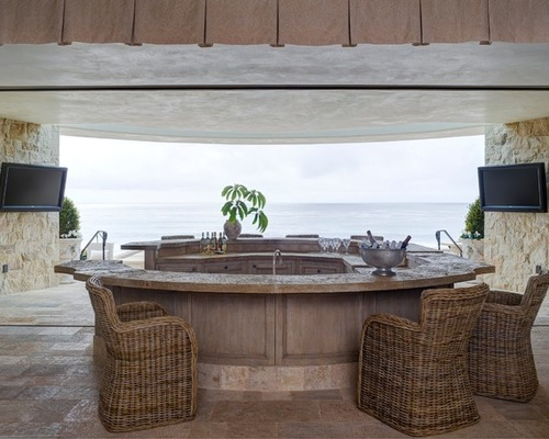 outdoor brown wet bar beside the sea with TV and sets of rattan chair and glasses to drink bottle of wine