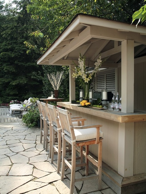 outdoor brown wooden wet bar with glasses and pot of flowers and sets of high brown wooden windsor chair with pillow