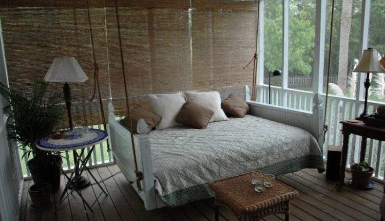 queen size bed swing with white comforter and two white pillows and three brown liwwos