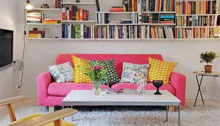 soft pink loveseat sofa with colorful accent pillows fury white rug minimalist white center table modern floating book rack