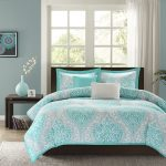 teal green bedding on brown bed