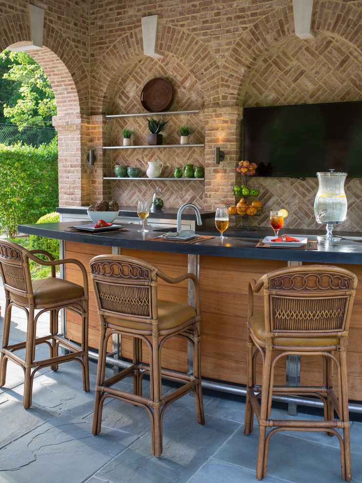 traditional wooden outdoor wet bar bricks walled with black countertop and brown rattan high stools with resting