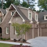 weathered wood colored brick wall grey roof white window 3 car garage
