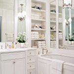 white bathroom ideas storage floor tile wall shelves cabinet vase flowers lighting faucet sink mirror hanging light