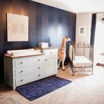 White Blue Theme Room Painted In Beige And Blue With Beige Rugs, Blue Mat, Golden Crib, White Cabinet With Diaper Changing Area On Top, Painting, And Big Girraffe Stuffed