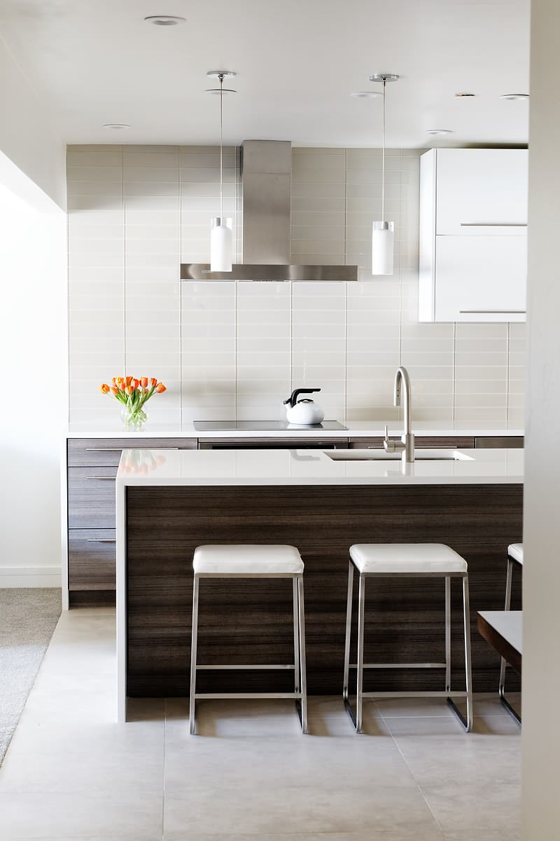 white glassy tiled backsplash upper white cabinet height dark wooden cabinet elegant minimalist lights