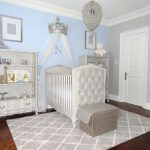 white theme room painted in light blue and grey with white cabinet for toys, white crib, white ottoman, silver king crown and curtain on top of the crib, crystal hanging lamp