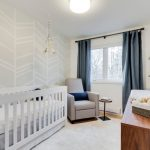White Theme Room With White Cirb, Grey Couch, Stag Head Paintings, Grey Curtain, Wooden Cabinet And Diaper Changing Area On Top Of It