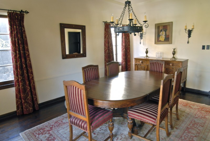 Colonial mediterranean dining room with wooden tabe set, white wall, wooden floor, red curtain, wrought iron chandelier