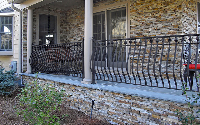 Mediterranean front porch with artistic black wrought iron railing system