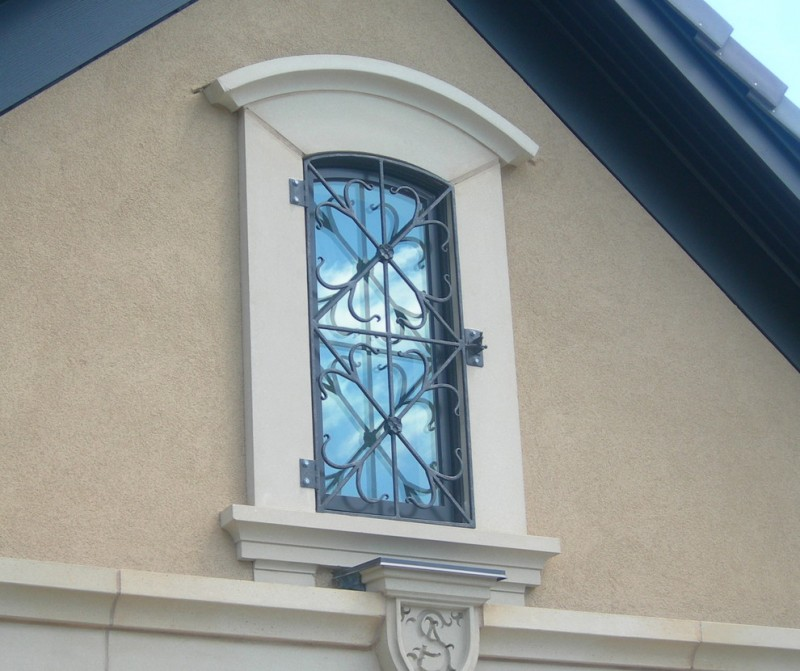artistic exterior window idea with custom black wrought iron bars addition
