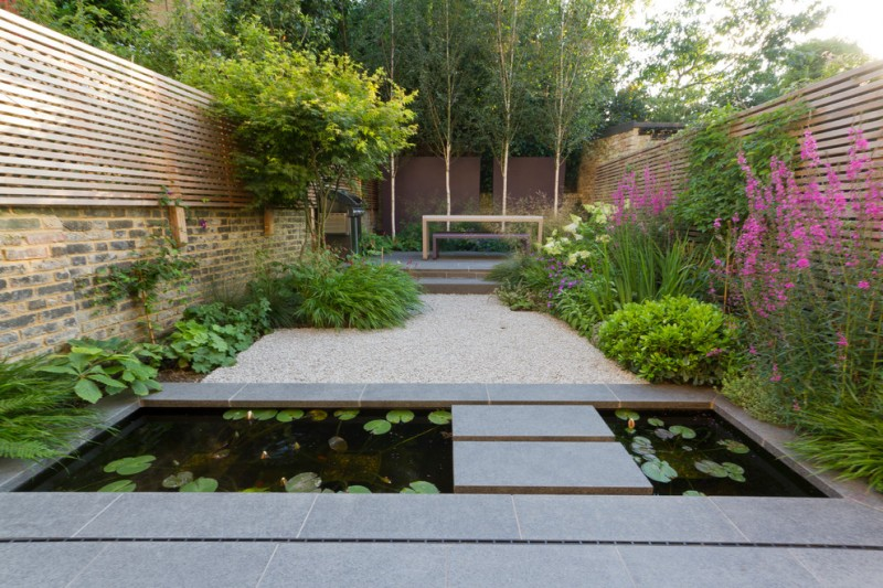 asian landscape backyard with wooden rails on top of the stone wall, pond with lotus and stepping pads, white river stones, a bench and a table, and trees and flowers on the side