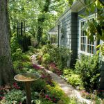 backyard full of shade trees and flowers with lime stones pathway, copper bird bath, wind chime
