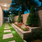 backyard with ceramic steppng stones, artificial grass, geranium and tree flower pots made by granite and copped by travertine