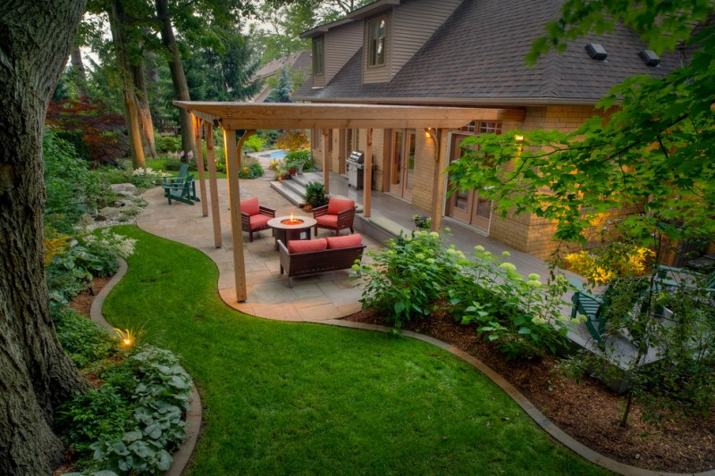 backyard with sitting area under opened wooden pergola, flagstone on concrete base pavement and plant edge, grass