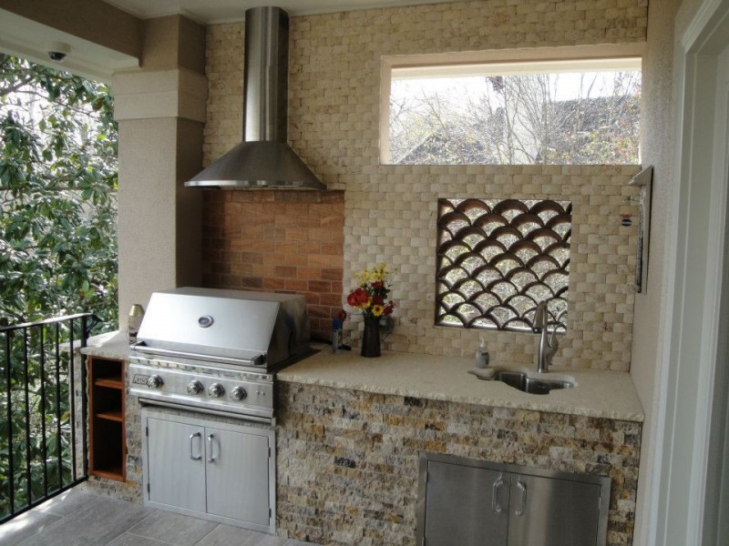 balcony summer kitchen with fisch scale window, brown tiles, brown stines under the sinks, cooker hood on top of barbeque grill