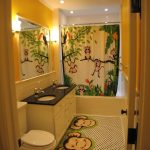 Bathroom With Monkey Mats, Monkey Curtain, Tile Flooring, White Cabinet With Black Counter Top, White Toilet, Yellow Wall