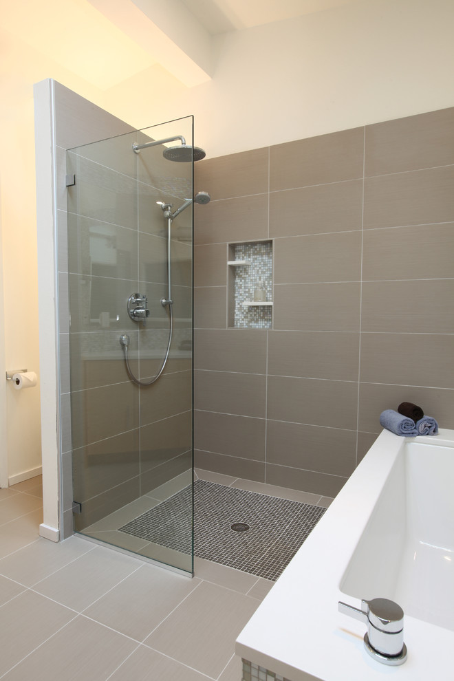 bathroom with walk in showers without door with mosaic tiles flooring, grey tiles wall and glass partition