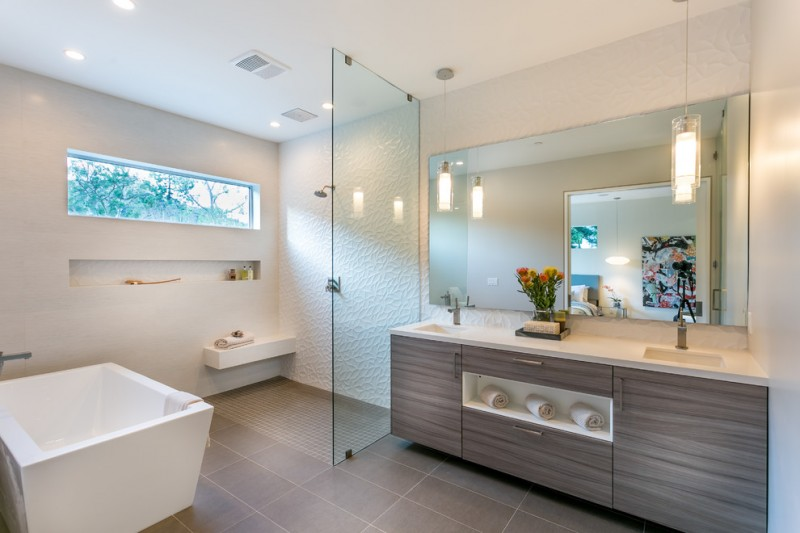 bathroom with walk in showers without door with white emboss wall in one side, glass partition to the sink area and without partition to the bathtub area
