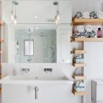 bathroom with white wall, white sink, white framed mirror, brown wooden shelves in right and left, two pendant lamps