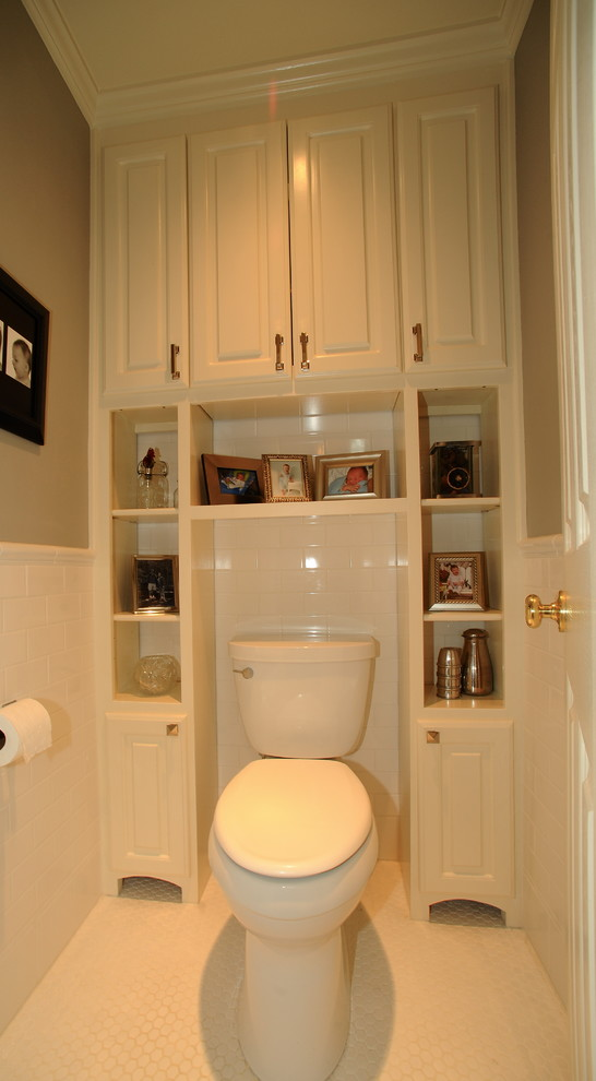 bathroom with white wall, white toilet, white shelves and white cabinet surrounded the toilet from the top