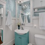bathroom with white wall, white toilet, white wooden framed mirror, turquoise cabinet
