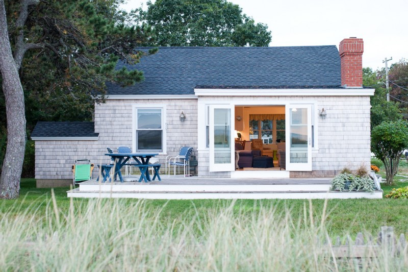 beach style small home in white stone outside wall with glass door and window, blue roof