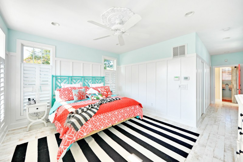 bed with turquoise headboard colorful bed sheet black & white stripes rug whitewashed floors light blue walls window with white shutters white ceiling white bedside table