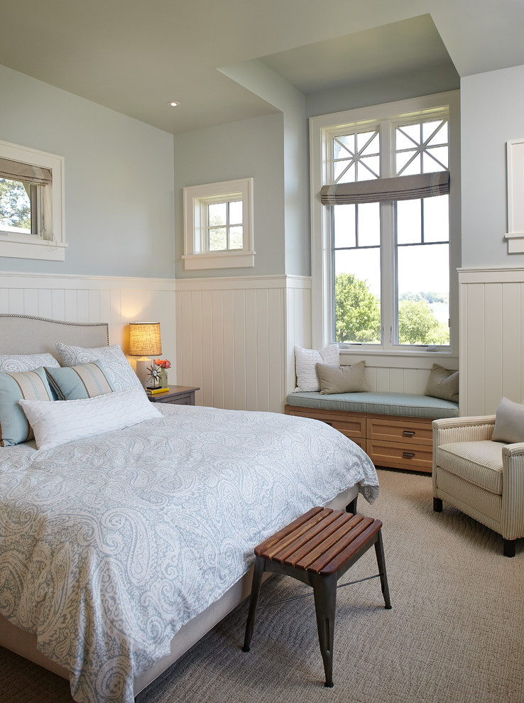 bedroom with blue painted half wall, white vertical wood paneling half bottom wall, brown rug, wooden bench, brown couch, white bedding, seating area in window nook with blue cushion and storage