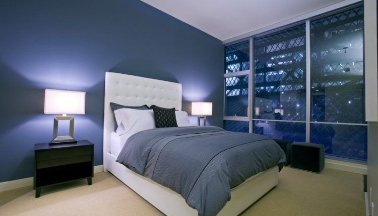 bedroom with blue walls, white ceiling, warm yellow rug, white bedding, blue bed cover, wood cabinet, table lamps