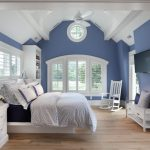 Bedroom With Blue Walls, White Vaulted Ceiling, White Chair, White Bench, White Cabinet, White Bedding, Navy Blue Linen, Light Blue Cover, White Framed Glass Window