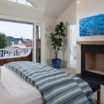 bedroom with door to balcony, white wall and ceiling, fireplace, plants, white blue bedding, brown rug, navy bench