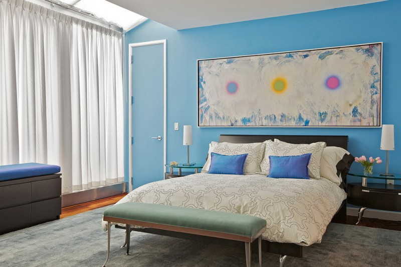 bedroom with light blue wall, wooden flooring, wooden storage chest with blue cushion, white curtain, white framed blue door, white bed cover with white and blue pillows, grey rug