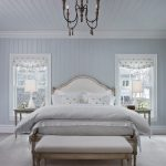 bedroom with soft blue painted wall, white bedding, white blue curtain, white bench, soft brown rug, chandelier