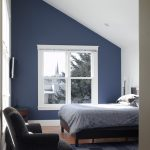 Bedroom With White Vaulted Ceiling, Navy Blue Walls, Wooden Flooring, Navy Blue Rug, Brown Couch, Dark Brown Side Table, Dark Brown Bedding, Light Blue Cover