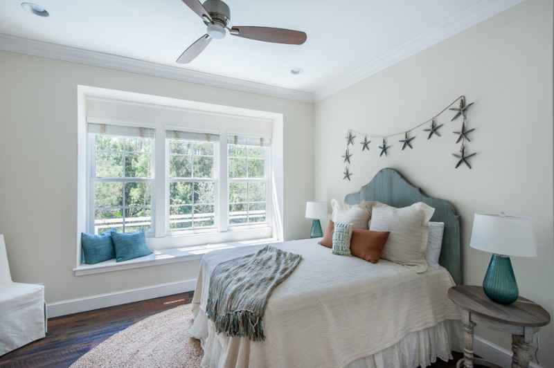 bedroom with white wall and ceiling, wooden flooring, white chair, white bed cover, teal bedding, side table, teal lamp, seating area in the window with teal pillows