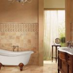 Beige Porcelain Tiles For Walls And Floors Free Standing Bathtub In White Traditional Bathroom Vanity With White Top Vessel Sink Gold Tone Faucet Frameless And Rounded Mirror